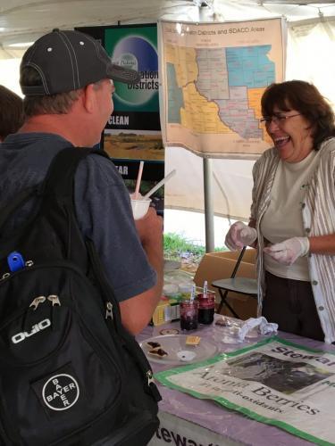 Jolene Stewart of Stewart's Aronia Acres samples haskaps & berries- Value Added Ag Day- S.D. State Fair 2019.